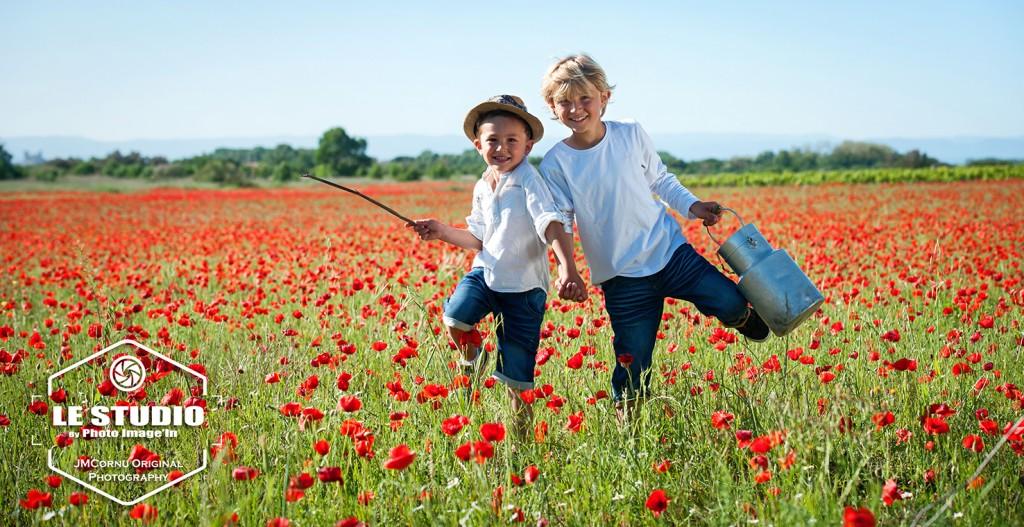 photo dans les coquelicot de deux enfants en train de courir avec un bidon de lait